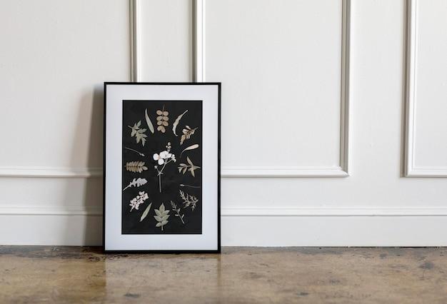 Maquette de cadre floral contre un mur blanc
