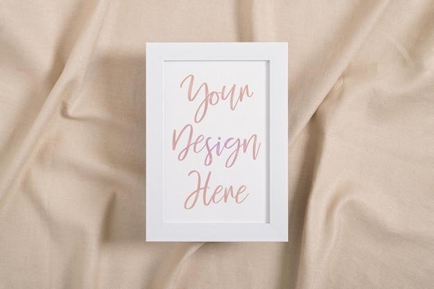 Maquette de cadre photo blanc sur une surface textile beige
