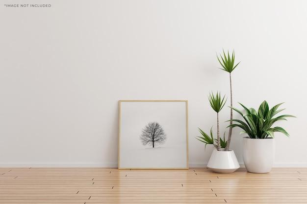 Maquette de cadre photo en bois carré sur une pièce vide de mur blanc avec des plantes sur un plancher en bois