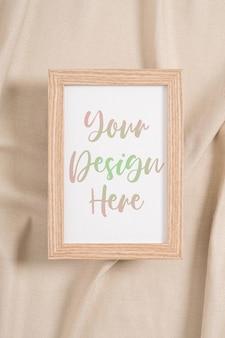 Maquette de cadre photo en bois sur un textile beige