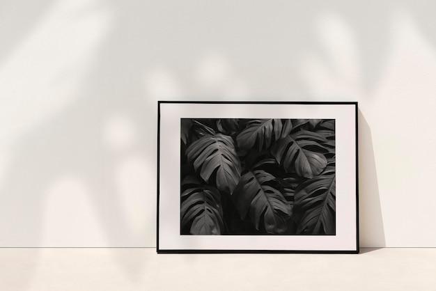 Maquette de cadre photo botanique psd appuyé contre le mur avec une ombre végétale