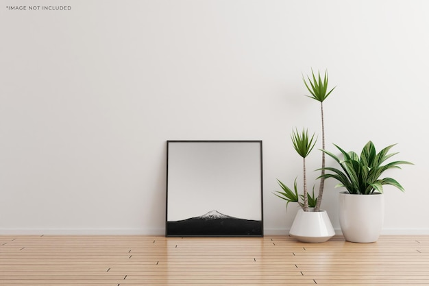 Maquette de cadre photo carré noir sur une pièce vide de mur blanc avec des plantes sur un plancher en bois