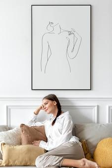 Maquette de cadre photo avec une femme se relaxant à la maison