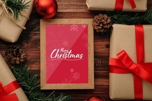 Maquette de cadre photo joyeux noël avec des décorations de cadeaux de noël