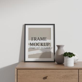 Maquette de cadre photo noir à côté de vases en céramique