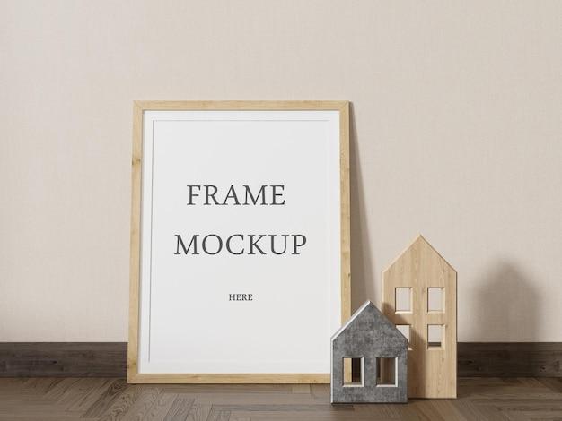 Maquette de cadre photo placée sur le sol à côté de petites figurines de maison