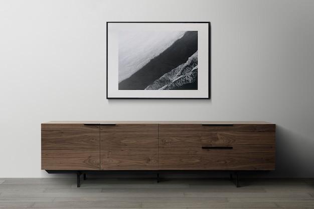 Maquette de cadre photo psd suspendue dans un intérieur de décoration de salon moderne