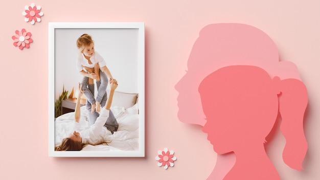 Maquette de cadre photo avec des silhouettes de maman et fille dans un style papier découpé pour la fête des mères