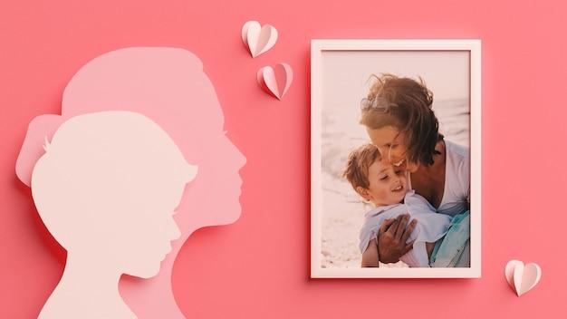 Maquette de cadre photo avec des silhouettes de maman et fils dans un style papier découpé pour la fête des mères