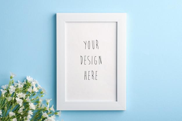 Maquette de cadre photo vide blanc avec des fleurs de mouron des oreilles de souris sur bleu