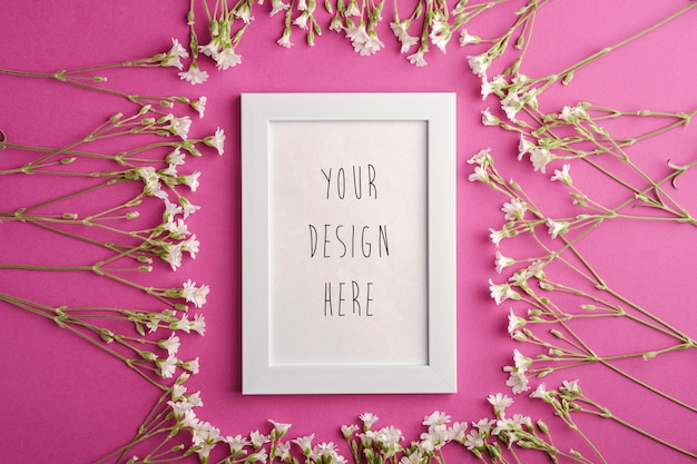 Maquette de cadre photo vide blanc avec des fleurs de mouron des oreilles de souris sur rose violet, vue de dessus