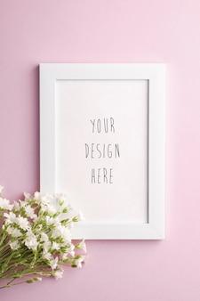 Maquette de cadre photo vide blanc avec des fleurs de mouron des oreilles de souris sur rose