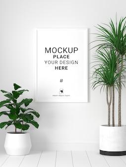 Maquette de cadre photo vierge avec plante en fond de mur blanc.