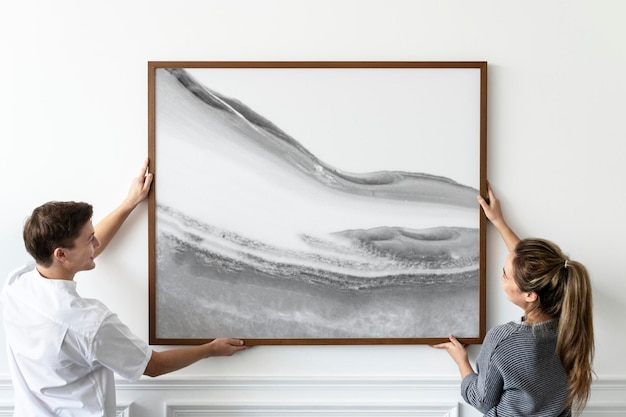 Maquette de cadre psd avec peinture abstraite accrochée par un couple