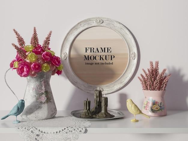 Maquette de cadre rond à côté de fleurs roses et jaunes