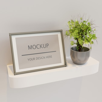 Maquette cadre vertical sur étagère murale avec plante