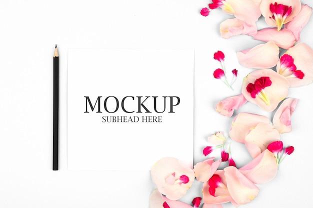 Maquette de cahier blanc et de beaux pétales de fleurs