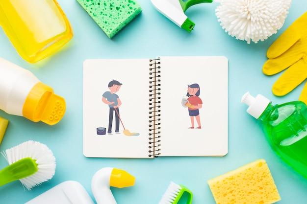 Maquette de cahier entourée d'outils de nettoyage