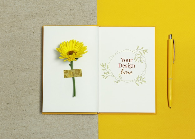 Maquette cahier sur fond beige jaune avec stylo et fleur d'été