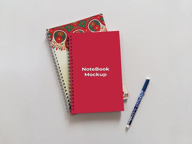 Maquette de cahier rouge portrait en spirale avec stylo