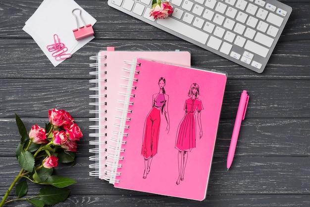 Maquette de cahier de vue de dessus et papeterie près des roses et du clavier