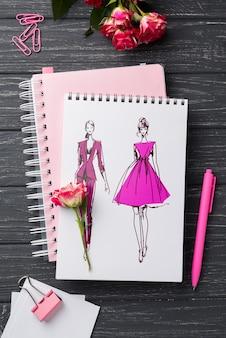 Maquette de cahier vue de dessus et papeterie près de roses
