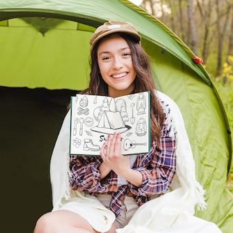 Maquette de camp d'été avec femme montrant un livre ouvert
