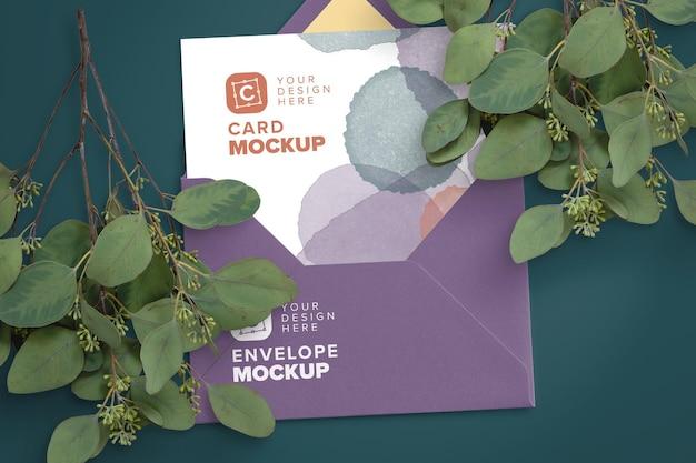 Maquette de carte de 5 x 7 pouces à l'intérieur d'une enveloppe avec des branches d'eucalyptus