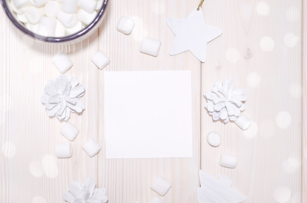 Maquette de carte carrée de noël avec des décorations blanches sur une table en bois blanc