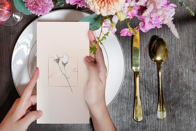 Maquette de carte d'invitation sur une assiette dans une réception