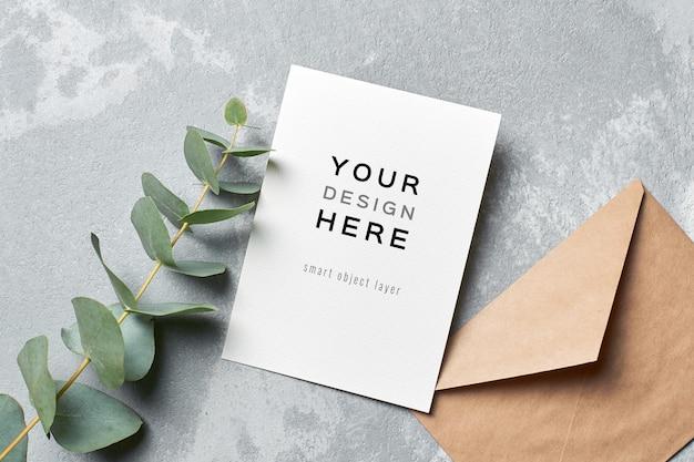 Maquette de carte d'invitation de mariage avec enveloppe et brindille d'eucalyptus sur fond de béton gris