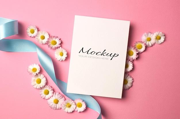 Maquette de carte d'invitation de mariage avec fleurs de marguerite et ruban turquoise sur rose
