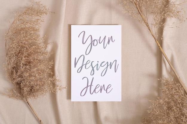 Maquette de carte papier blanc blanc avec de l'herbe sèche de la pampa sur un textile de couleur neutre beige