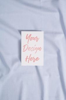 Maquette de carte papier blanc blanc sur un textile de couleur neutre bleu