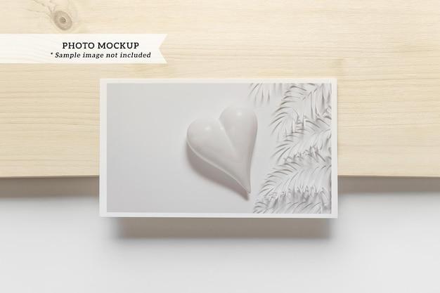 Maquette de carte photo sur fond de papier en bois et blanc