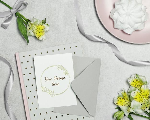 Maquette carte postale sur fond gris avec des fleurs, un gâteau et un ruban