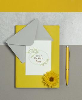 Maquette carte postale avec des notes jaunes, une enveloppe grise et un stylo