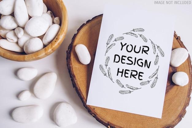 Maquette de carte postale verticale boho avec galet blanc et section coupée en bois sur fond de tableau blanc. image bohème rustique. espace pour le texte. copyspace maquette
