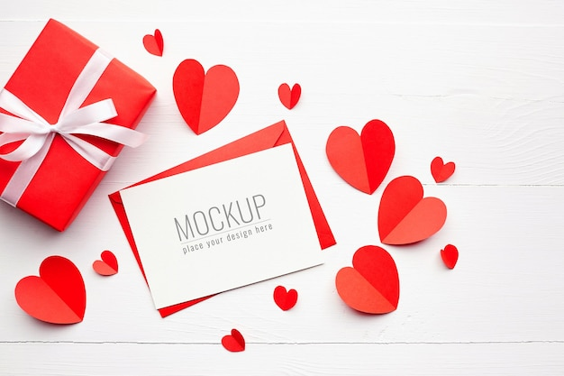 Maquette de carte de saint valentin avec boîte-cadeau et coeurs rouges sur blanc