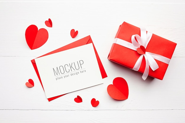 Maquette de carte de la saint-valentin avec boîte-cadeau et coeurs rouges