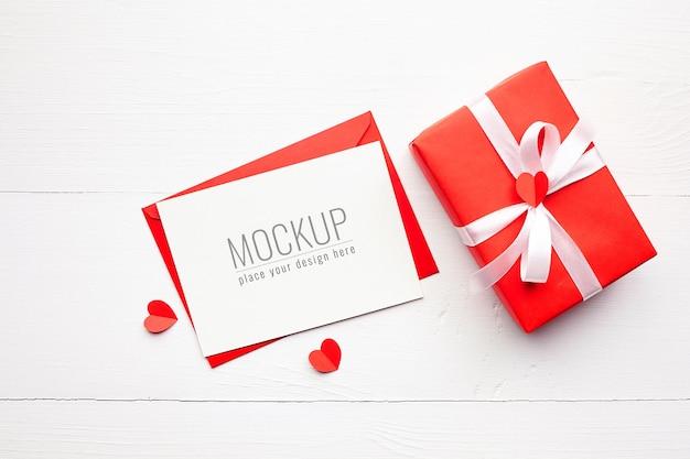 Maquette de carte saint valentin avec boîte-cadeau rouge et coeurs sur blanc