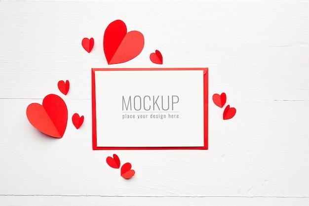 Maquette de carte saint valentin avec coeurs en papier rouge sur blanc