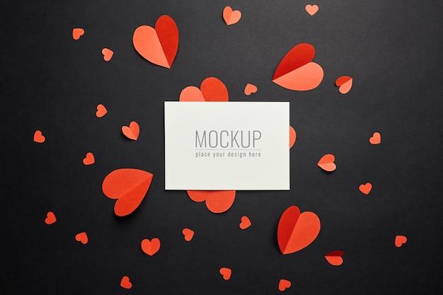Maquette de carte saint valentin avec des coeurs en papier rouge sur une surface noire