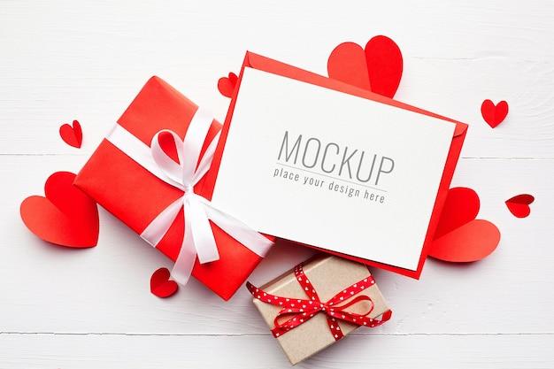 Maquette de carte saint valentin avec coffrets cadeaux et coeurs en papier rouge sur surface blanche