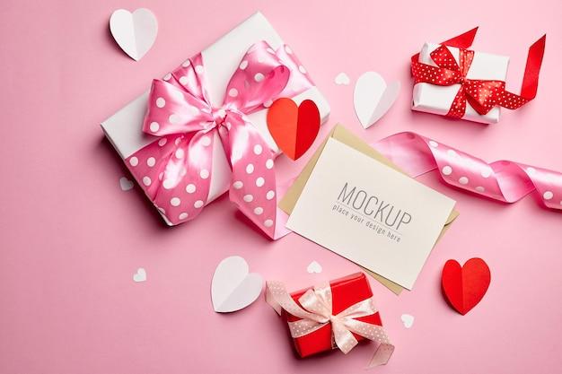 Maquette de carte saint valentin avec coffrets cadeaux et coeurs sur surface rose