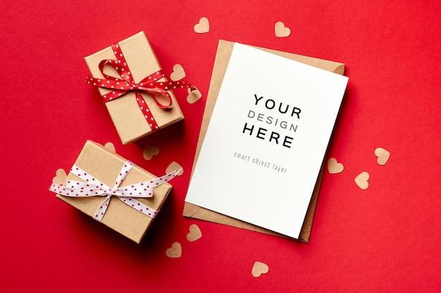 Maquette de carte saint valentin avec coffrets cadeaux et petits coeurs en papier sur rouge