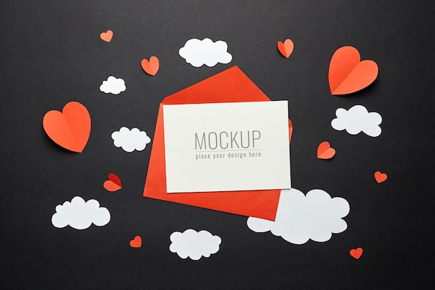 Maquette de carte saint valentin avec des décorations en papier sur une surface noire