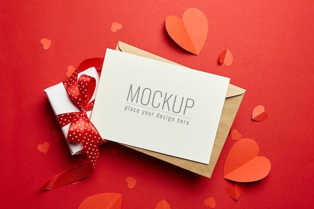 Maquette de carte de saint valentin avec enveloppe, boîte-cadeau et coeurs en papier rouge