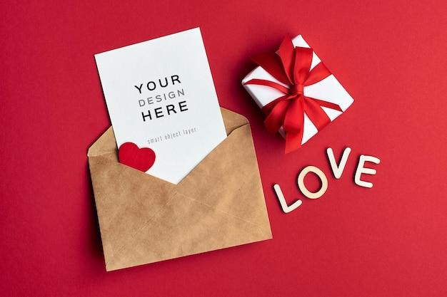 Maquette de carte de saint valentin avec enveloppe et boîte-cadeau sur rouge
