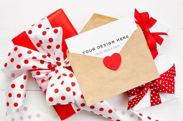 Maquette de carte saint valentin avec enveloppe, coeur rouge et coffrets cadeaux